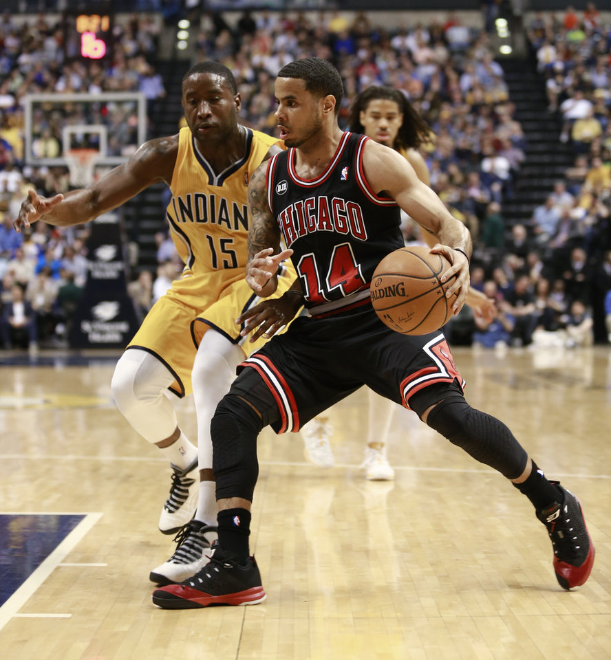 Photo - Chicago Bulls guard D.J. Augustin (14) drives on Indiana Pacers guard Donald Sloan in the first half of an NBA basketball game in Indianapolis, Friday, March 21, 2014. (AP Photo/R Brent Smith)