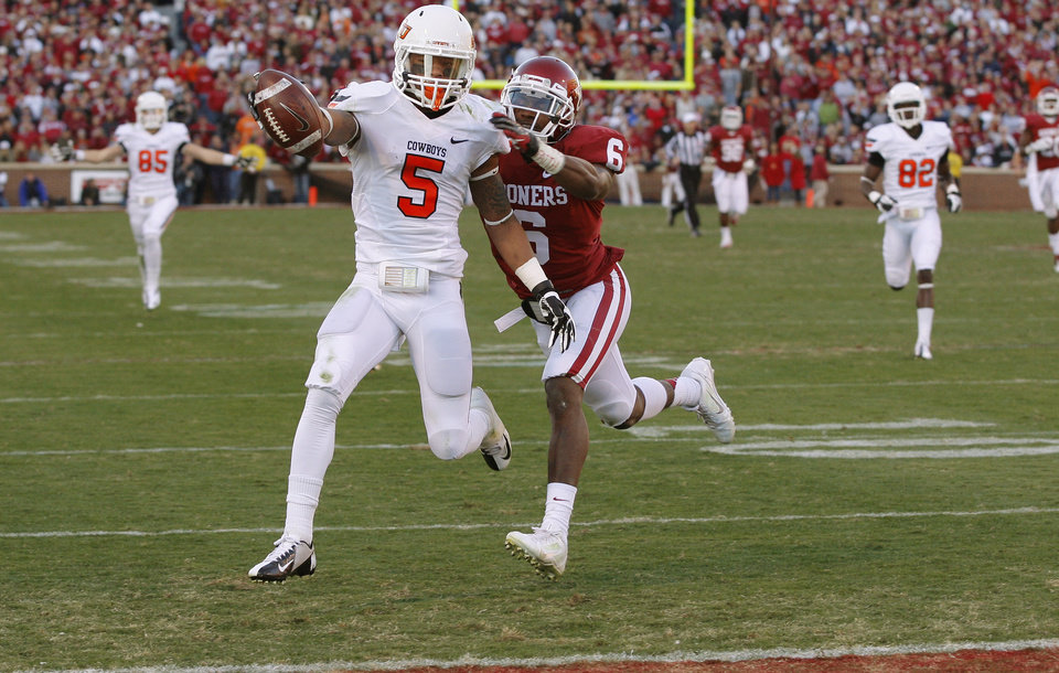 Photo - Oklahoma State's Josh Stewart (5) scores a touchdown past Oklahoma's Demontre Hurst (6) during the Bedlam college football game between the University of Oklahoma Sooners (OU) and the Oklahoma State University Cowboys (OSU) at Gaylord Family-Oklahoma Memorial Stadium in Norman, Okla., Saturday, Nov. 24, 2012. Oklahoma won 51-48. Photo by Bryan Terry, The Oklahoman