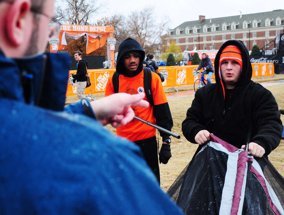 Photo - Oklahoma State students Kyle McAreavy (left) and Chase Chambers (right) set up a tent in preparation for ESPN's traveling show College Gameday that completed set up on Friday for their broadcast Saturday morning, November 23, 2013 from Oklahoma State's library lawn. Photo by KT King/For the Tulsa World