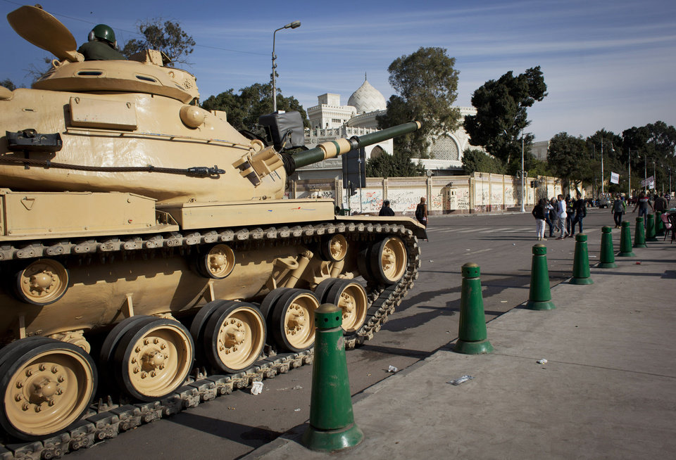 An Egyptian army soldiers sits atop a military tank in front of the presidential palace, in Cairo, Egypt, Sunday, Dec. 9, 2012. Egypt's liberal opposition has called for more protests on Sunday after the president made concessions overnight that fell short of their demands to rescind a draft constitution going to a referendum on Dec. 15. (AP Photo/Nasser Nasser)