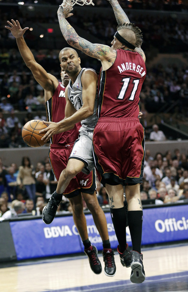 Photo - San Antonio Spurs' Tony Parker, center, of France, is defended by Miami Heat's Chris Andersen (11) and Shane Battier, left, as he drives to the basket during the first half of an NBA basketball game, Sunday, March 31, 2013, in San Antonio. (AP Photo/Eric Gay)