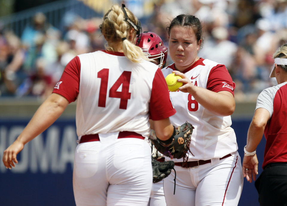 Photo - Oklahoma starting pitcher Paige Parker (8) gives the ball to Paige Lowary (14) in the top of the fifth inning during the second game of the Women's College World Series between the Oklahoma Sooners (OU) and Washington Huskies at USA Softball Hall of Fame Stadium in Oklahoma City, Thursday, May 31, 2018. Washington won 2-0. Photo by Nate Billings, The Oklahoman
