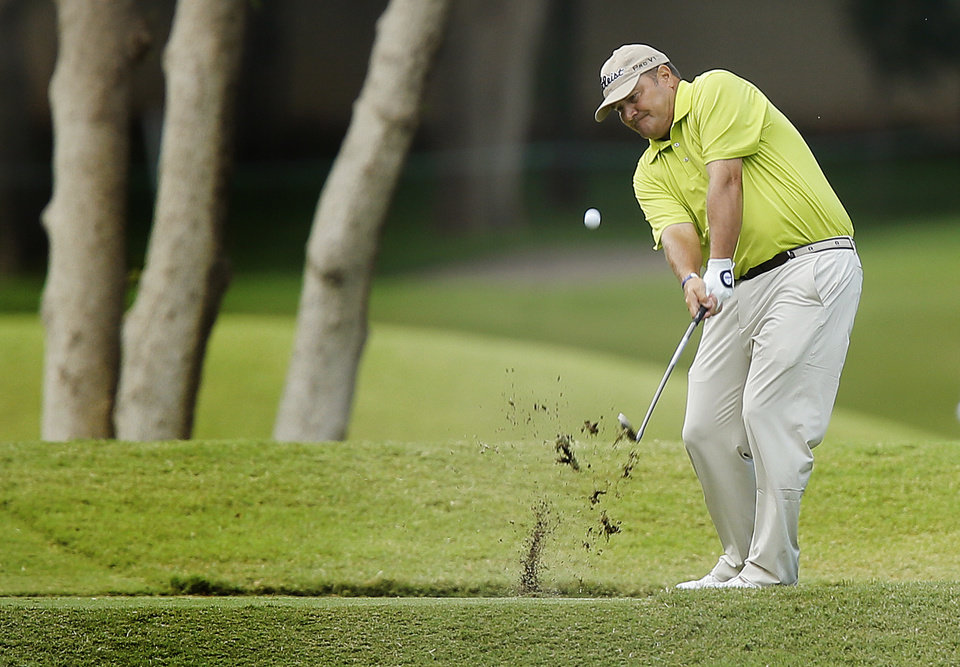 Photo - Rocky Walcher hits a shot during the first round of the U.S. Senior Open Championship golf tournament at Oak Tree National in Edmond, Okla. on Thursday, July 10, 2014. Photo by Chris Landsberger, The Oklahoman