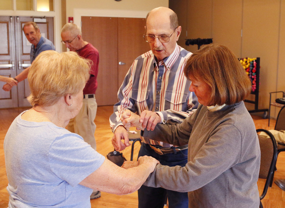 Photo -  Betty Windsor, left, and Patty Snyder receive instruction from Gene Schultingkemper, a sixth-degree black belt, during a basic awareness self-defense class at the Edmond Senior Center. PHOTO BY PAUL HELLSTERN, THE OKLAHOMAN   PAUL HELLSTERN -