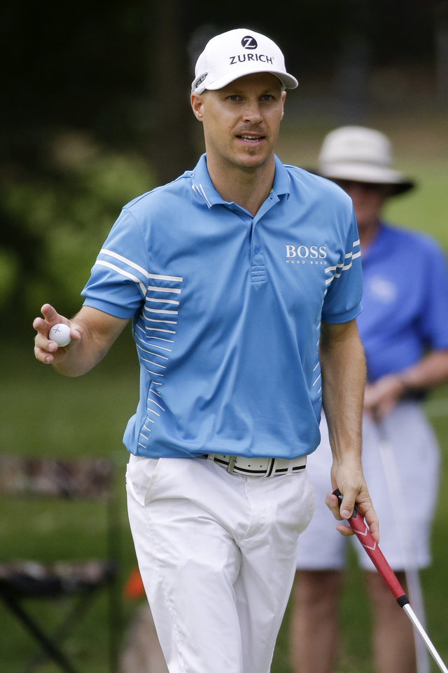 Photo - Ben Crane acknowledges the crowd after making his par putt on the 17th green during the third round of the St. Jude Classic golf tournament, Sunday, June 8, 2014, in Memphis, Tenn. Weather delays during the week forced Saturday's third round to be finished Sunday morning before the final round could begin. (AP Photo/Mark Humphrey)