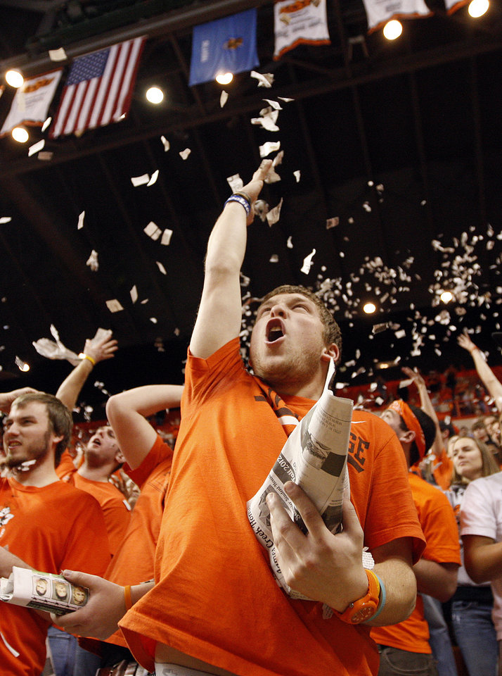 Photo - OSU sophomore Derek Hatridge of Kiowa, Okla., tosses pieces of newspaper in the air as the Cowboys are introduced before the Bedlam men's college basketball game between the Oklahoma State University Cowboys and the University of Oklahoma Sooners at Gallagher-Iba Arena in Stillwater, Okla., Monday, Jan. 9, 2012. Photo by Nate Billings, The Oklahoman