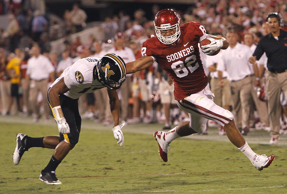 Photo - Oklahoma's Tanner Gillette (82) stiff arms Missouri's Matt White (17) during the college football game between the University of Oklahoma Sooners (OU) and the University of Missouri Tigers (MU) at the Gaylord Family-Memorial Stadium on Saturday, Sept. 24, 2011, in Norman, Okla. Photo by Chris Landsberger, The Oklahoman