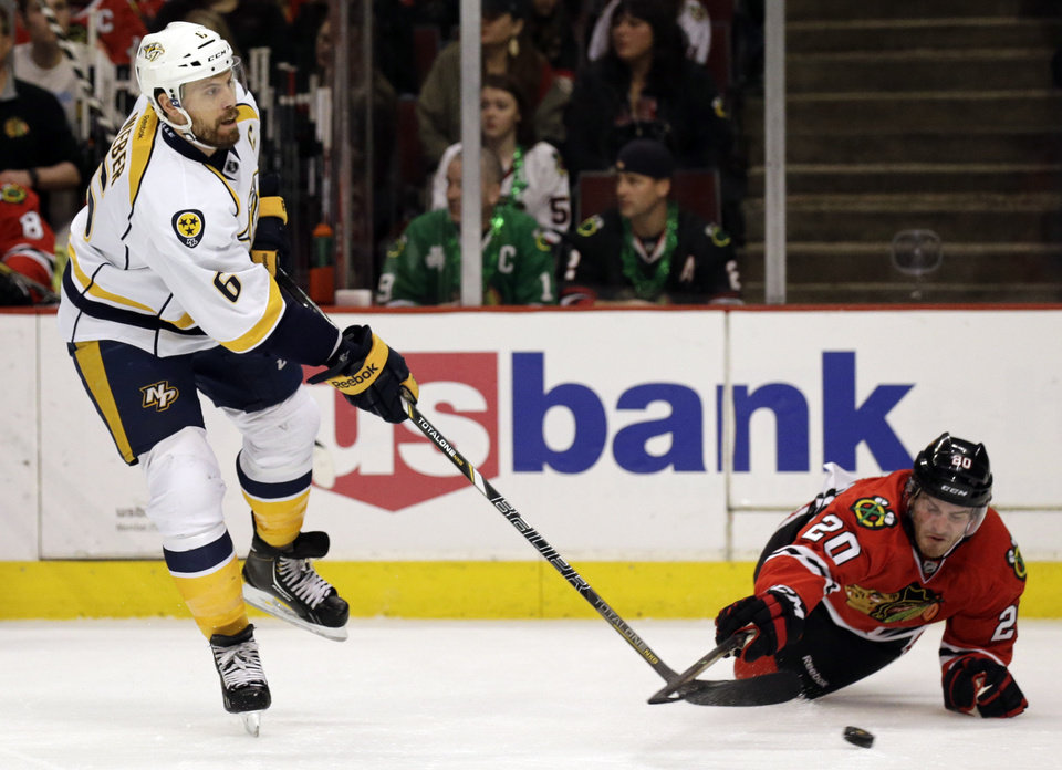 Photo - Nashville Predators' Shea Weber (6), left, passes against Chicago Blackhawks' Brandon Saad (20) during the first period of an NHL hockey game in Chicago, Friday, March 14, 2014. (AP Photo/Nam Y. Huh)