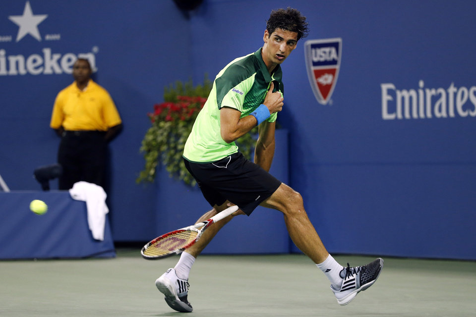Photo - Thomaz Bellucci, of Brazil, hits a shot between his legs to Stan Wawrinka, of Switzerland, during the second round of the U.S. Open tennis tournament Wednesday, Aug. 27, 2014, in New York. (AP Photo/Jason DeCrow)