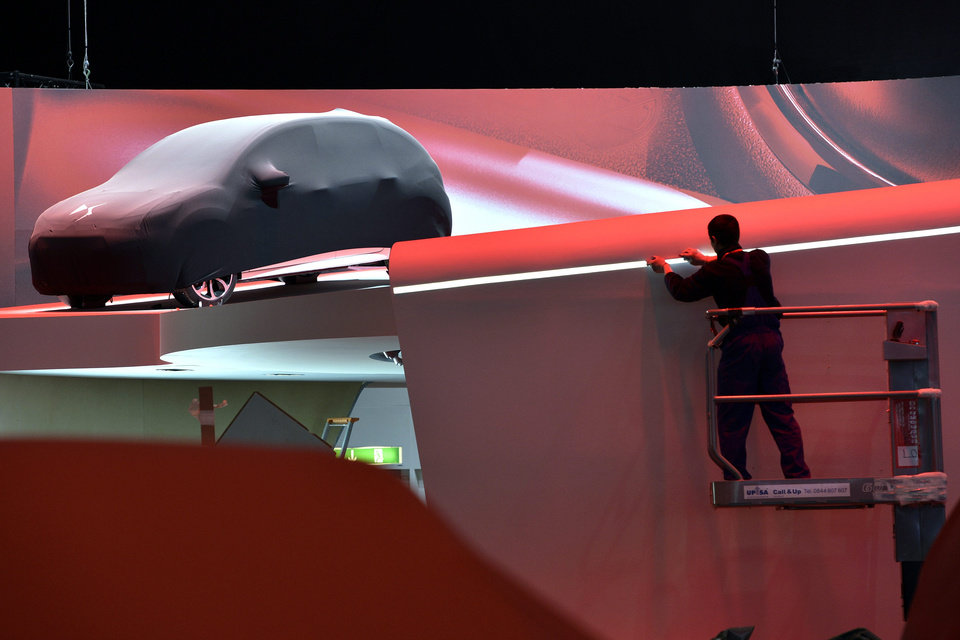 Photo - A worker is busy at the Citroen booth next to a car during last preparations prior to the opening of the press preview days at the 83nd Geneva International Motor Show in Geneva, Switzerland, Saturday, March 2, 2013. The Motor Show will open its gates to the public from March 7 to 17, presenting more than 260 exhibitors and more than 130 world and European premieres. (AP Photo/Keystone, Martial Trezzini)