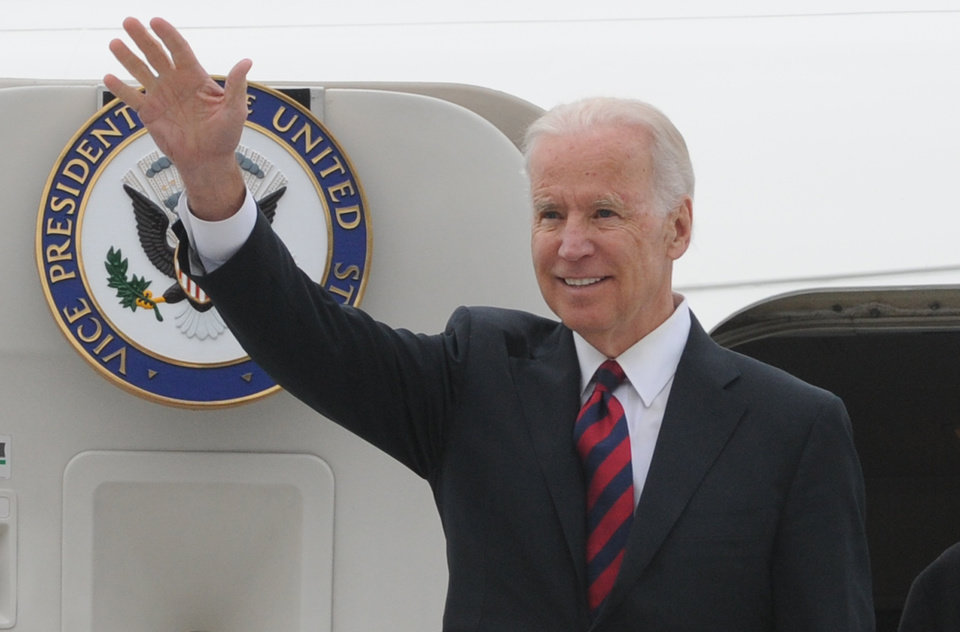 Photo - U.S. Vice President Joe Biden waves as he arrives at the Okecie military airport in Warsaw, Poland, Tuesday, March 18, 2014. Biden arrived in Warsaw for consultations with Polish Prime Minister Donald Tusk and President Bronislaw Komorowski, a few hours after Russian President Vladimir Putin approved a draft bill for the annexation of Crimea, one of a flurry of steps to formally take over the Black Sea peninsula. (AP Photo/Alik Keplicz)