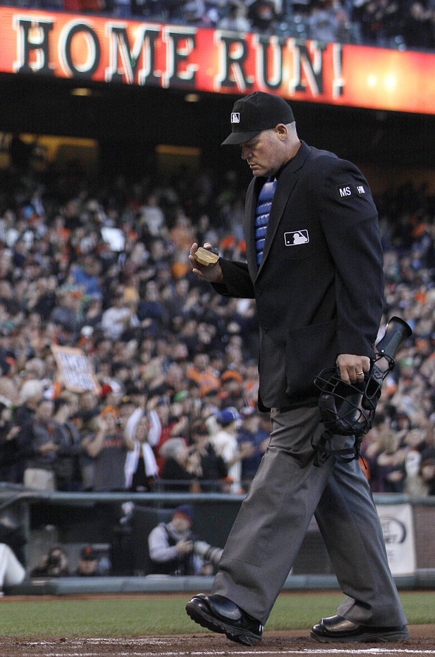 Photo -   Home plate umpire Ted Barrett stands over home plate after San Francisco Giants first baseman Brandon Belt hit a two-run home run off of Houston Astros pitcher J.A. Happ during the second inning of a baseball game in San Francisco, Wednesday, June 13, 2012. Barrett was behind the plate Wednesday night when San Francisco Giants' right-hander Matt Cain pitched a perfect game against the Houston Astros in a 10-0 victory. He also was the home plate umpire when David Cone threw his perfect game for the New York Yankees in a 6-0 win over the Montreal Expos on July 18, 1999. It makes Barrett the first major league umpire to call balls and strikes for two perfect games. (AP Photo/Jeff Chiu)