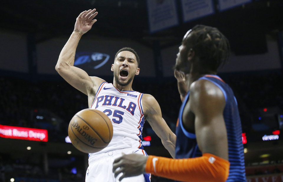 Photo - Philadelphia 76ers guard Ben Simmons (25) shouts in front of Oklahoma City Thunder forward Jerami Grant, right, after a dunk during the first half of an NBA basketball game Thursday, Feb. 28, 2019, in Oklahoma City. (AP Photo/Sue Ogrocki)