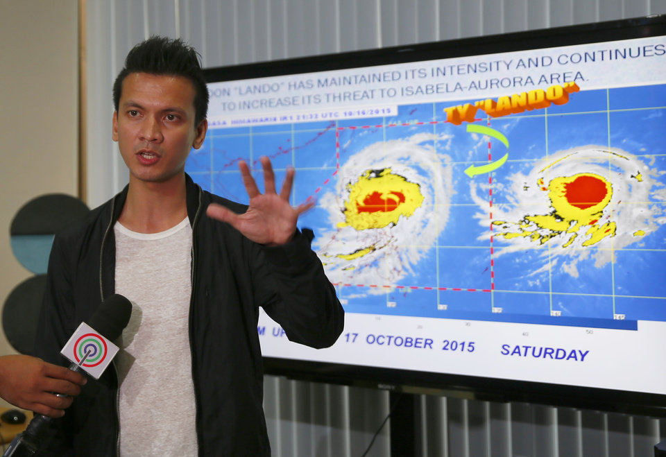 Photo - Weather Bureau forecaster Aldczar Aurelio gestures during a media briefing on Typhoon Koppu Saturday, Oct. 17, 2015 at suburban Quezon city, northeast of Manila, Philippines. Typhoon Koppu, packing sustained winds of 160 kilometers (100 miles) per hour and gusts of up to 190 kph (119 mph) early Saturday about 300 kilometers (188 miles) east of Aurora province in northeastern Philippines, is forecast to make landfall early Sunday. Disaster officials advised communities in flood-prone areas of the northern Philippines to evacuate Saturday as the slow-moving typhoon bore down on the coast with heavy rains and high winds. (AP Photo/Bullit Marquez)