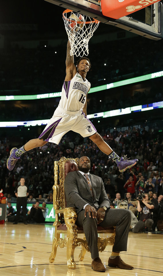 Photo - Ben McLemore of the Sacramento Kings dunks the ball as he flies over former NBA player Shaquille O'Neal during the skills competition at the NBA All Star basketball game, Saturday, Feb. 15, 2014, in New Orleans. (AP Photo/Gerald Herbert)