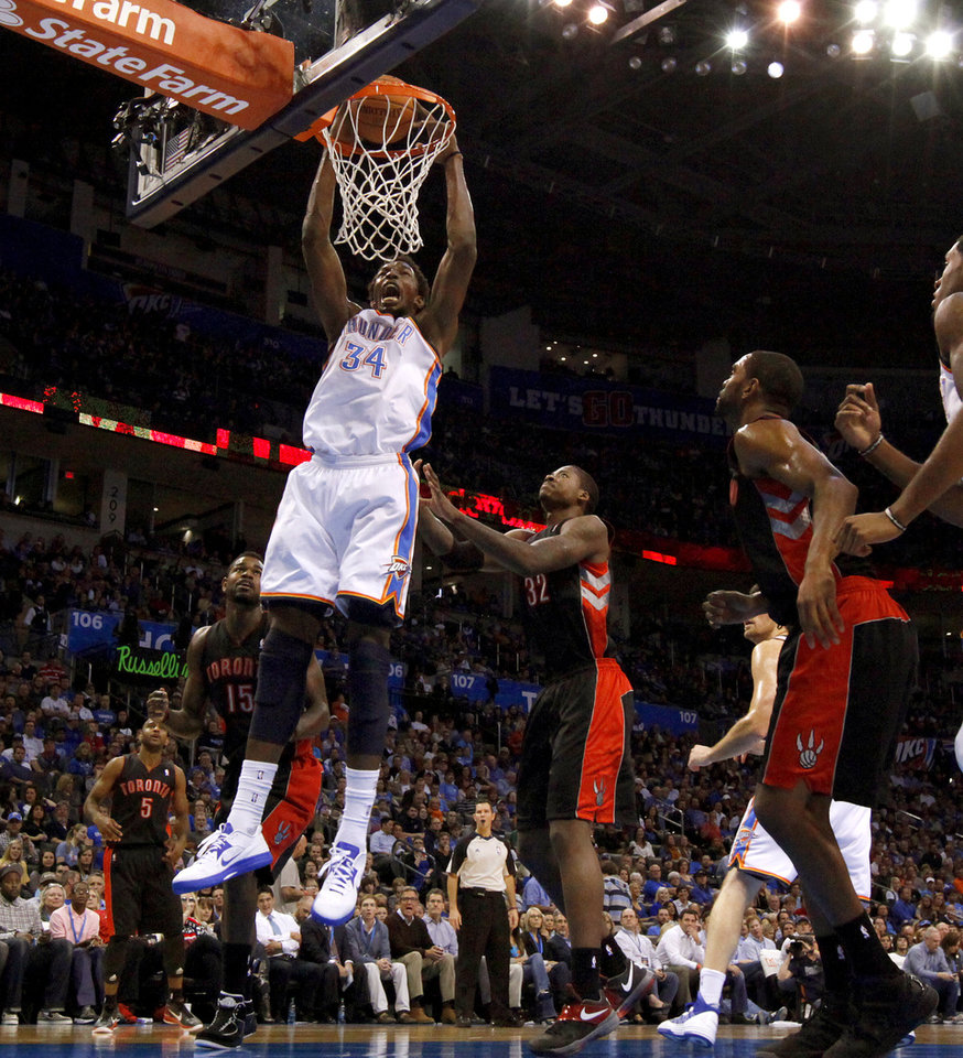 Photo - Oklahoma City's Hasheem Thabeet (34) dunks the ball beside Toronto's Ed Davis (32) during an NBA basketball game between the Oklahoma City Thunder and the Toronto Raptors at Chesapeake Energy Arena in Oklahoma City, Tuesday, Nov. 6, 2012.  Tuesday, Nov. 6, 2012. Oklahoma City won 108-88. Photo by Bryan Terry, The Oklahoman