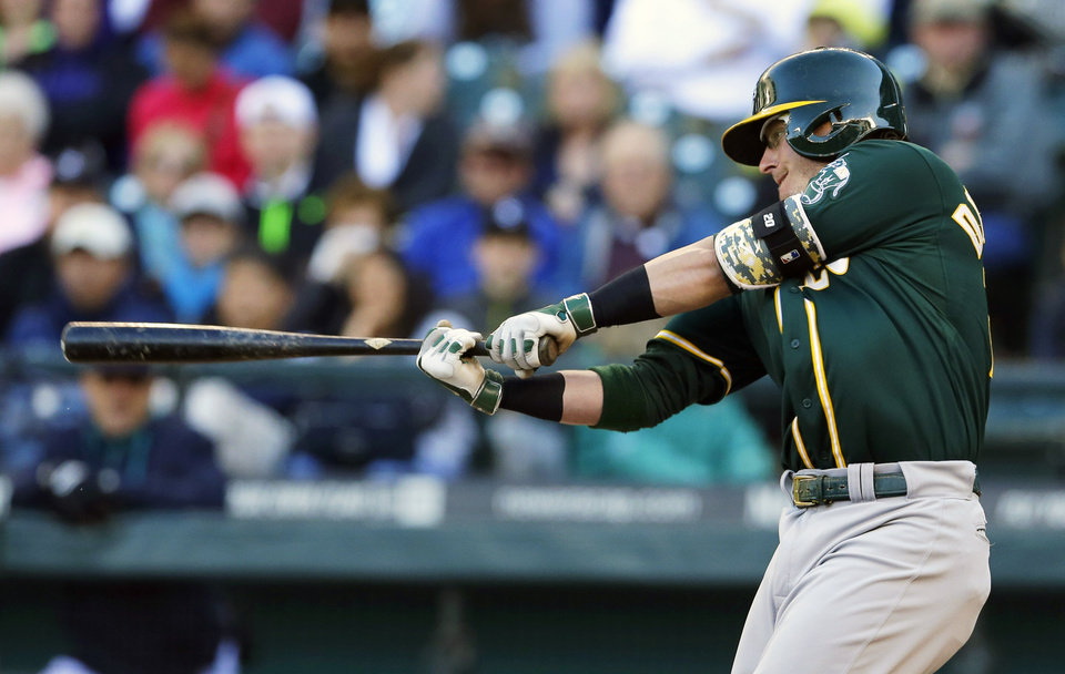 Photo - Oakland Athletics' Josh Donaldson hits a two-run home run in the first inning of a baseball game against the Seattle Mariners, Saturday, April 12, 2014, in Seattle. (AP Photo/Ted S. Warren)