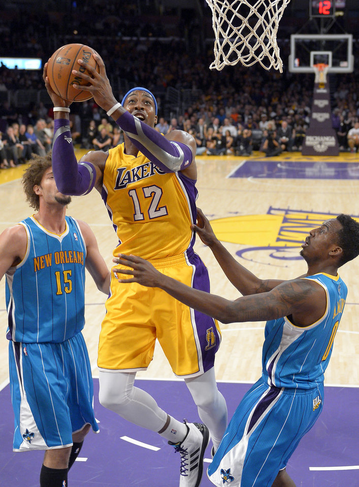 Los Angeles Lakers center Dwight Howard puts up a shot as New Orleans Hornets forward Al-Farouq Aminu, right, and center Robin Lopez defend during the first half of an NBA basketball game, Tuesday, Jan. 29, 2013, in Los Angeles. (AP Photo/Mark J. Terrill)