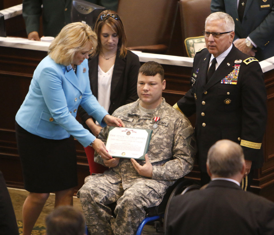 Photo -  Above: Gov. Mary Fallin and Maj. Gen. Myles Deering, Oklahoma adjutant general, present a medal and commendation to Sgt. E.H. Pittman during a joint session of the Legislature on Tuesday in Oklahoma City. Pittman, also shown with his wife, Jean, suffered major injuries while protecting others inside a 7-Eleven during the May 20 tornado in Moore.    PAUL HELLSTERN -