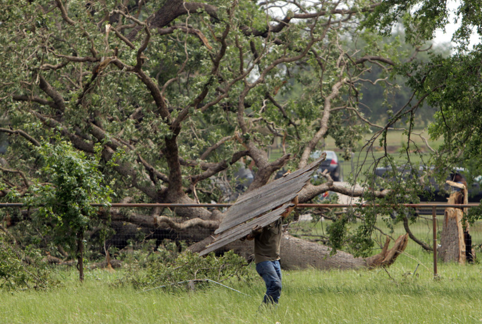 Photo - Eric Montez cleans up his place in Granbury, Texas, Friday, May 17, 2013. On Wednesday an EF-4 tornado hit the small north Texas town. (AP Photo/Mike Fuentes)