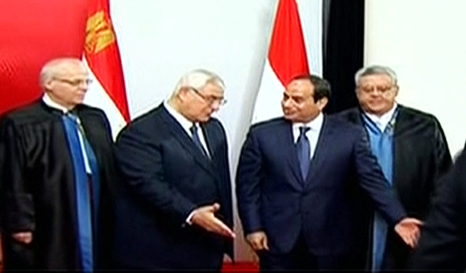 Photo - This image made from Egyptian State Television shows newly sworn in President Abdel-Fattah el-Sissi, right, and outgoing interim President Adly Mansour, center left, leaving after a ceremony at the Supreme Constitutional Court in Cairo, Egypt, Sunday, June 8, 2014. El-Sissi's inauguration Sunday comes less than a year after the 59-year-old career infantry officer ousted the country's first freely elected president, the Islamist Mohammed Morsi, following days of mass protests by Egyptians demanding he step down. (AP Photo/Egyptian State Television)