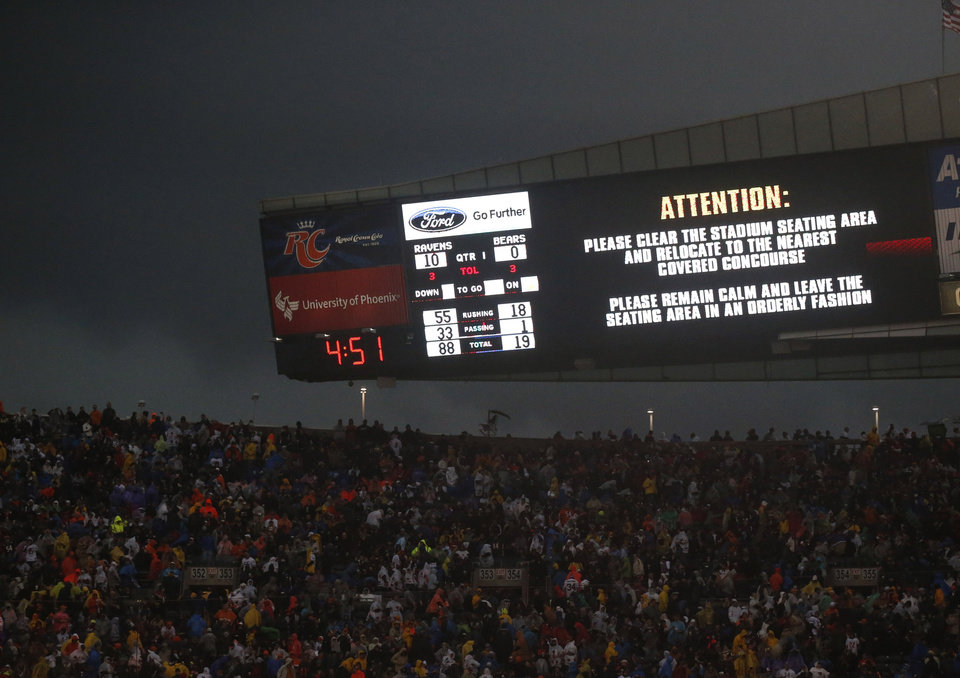 Photo - Fans are warned to take cover as a severe storm moves through Soldier Field during the first half of an NFL football game between the Chicago Bears and Baltimore Ravens, Sunday, Nov. 17, 2013, in Chicago. (AP Photo/Charles Rex Arbogast)
