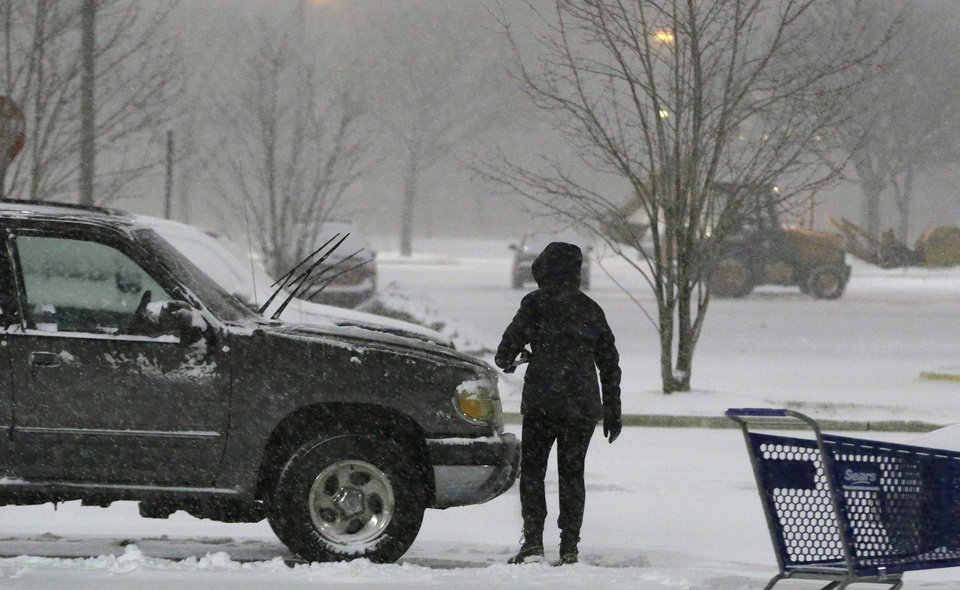 Photo - A person brushes snow off a vehicle in the parking lot of Willowbrook Mall, Thursday, Jan. 2, 2014, in Wayne, N.J. Snow and bone-chilling temperatures are expected for the overnight hours with substantial accumulation predicted. (AP Photo/Julio Cortez)