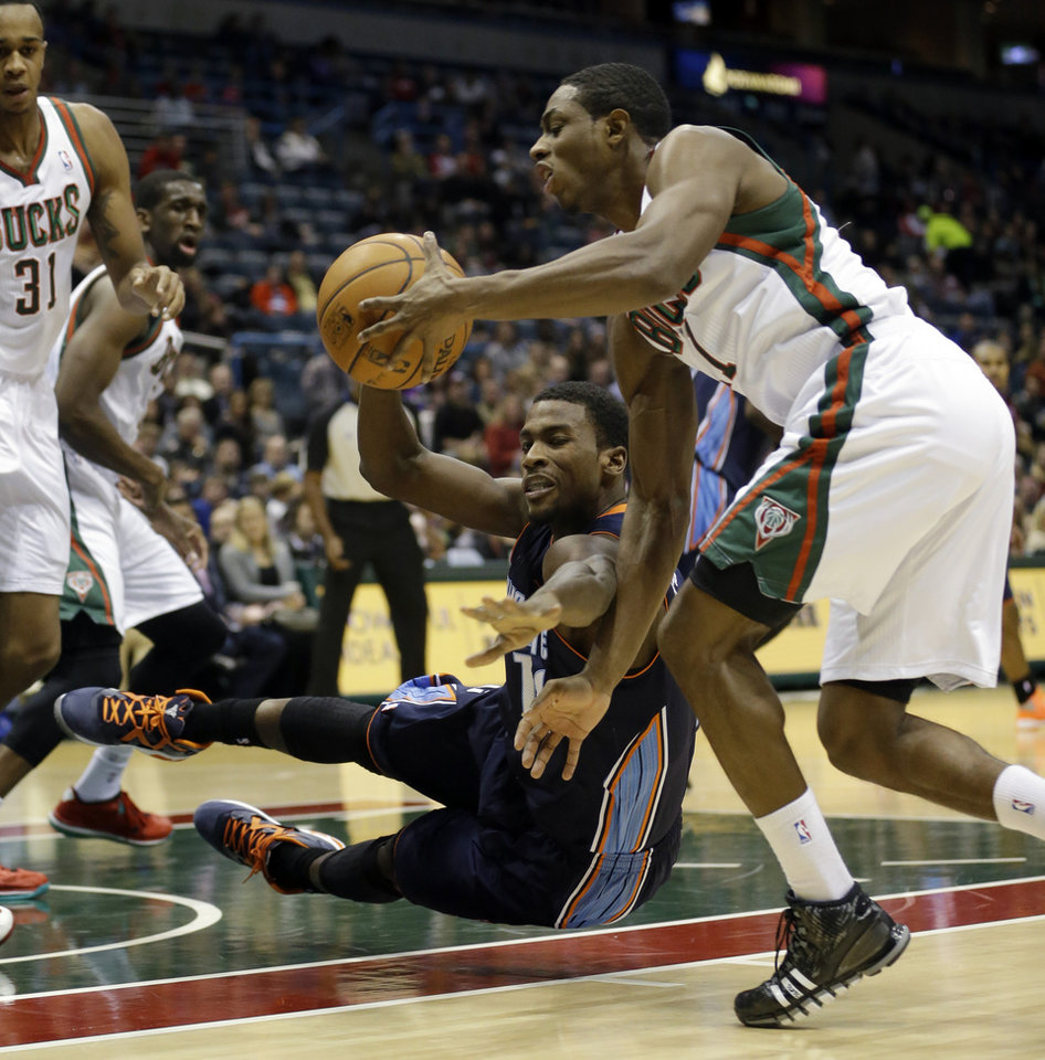 Photo - Charlotte Bobcats' Michael Kidd-Gilchrist, center, and Milwaukee Bucks' Brandon Knight, right, go after a loose ball during the first half of an NBA basketball game on Saturday, Nov. 23, 2013, in Milwaukee. (AP Photo/Morry Gash)