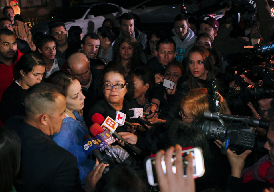 Rosie Rivera, sister of singer Jenni Rivera, hugs their mother Rosa Rivera, as Pastor Pedro Rivera Jr., left, watches during a news conference with friends and family outside the home of Rivera's father in Lakewood, Calif., on Sunday, Dec. 9, 2012. Authorities have not confirmed her death, but Rivera�s relatives in the U.S. say they have few doubts that she was on the Learjet 25 that disintegrated on impact Sunday in rugged territory in Nuevo Leon state in northern Mexico. (AP Photo/Patrick T. Fallon)