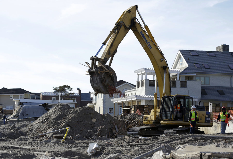 Photo - The remains of a house damaged by Superstorm Sandy and then bulldozed by a contractor are removed from the beach in the Belle Harbor section of the Rockaways, as cleanup from the storm continues Thursday, Jan. 10, 2013, in New York. (AP Photo/Kathy Willens)