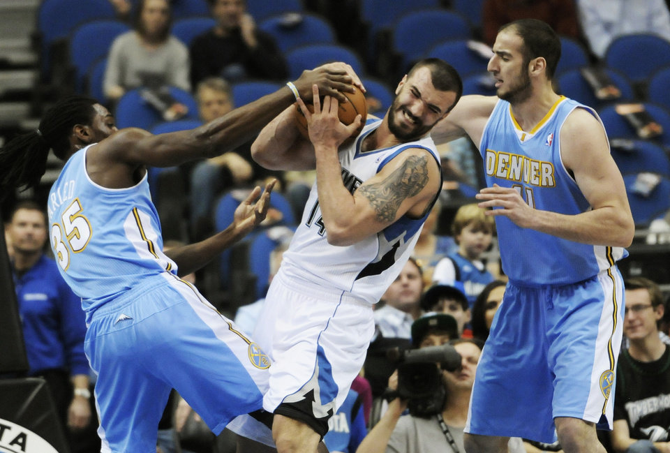 Photo -   Minnesota Timberwolves' Nikola Pekovic, center, of Montenegro, tries to hang onto the ball as he tussles with Denver Nuggets' Kosta Koufos, right, and Kenneth Faried, left, in the first half of an NBA basketball game on Wednesday, Nov. 21, 2012, in St. Paul. (AP Photo/Jim Mone)