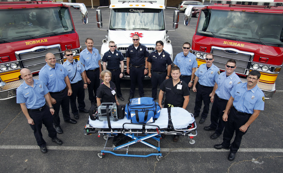 Photo - Norman firefighters, emergency room nurses and paramedics pose in front of emergency vehicles at their headquarters. PHOTO BY STEVE SISNEY, THE OKLAHOMAN