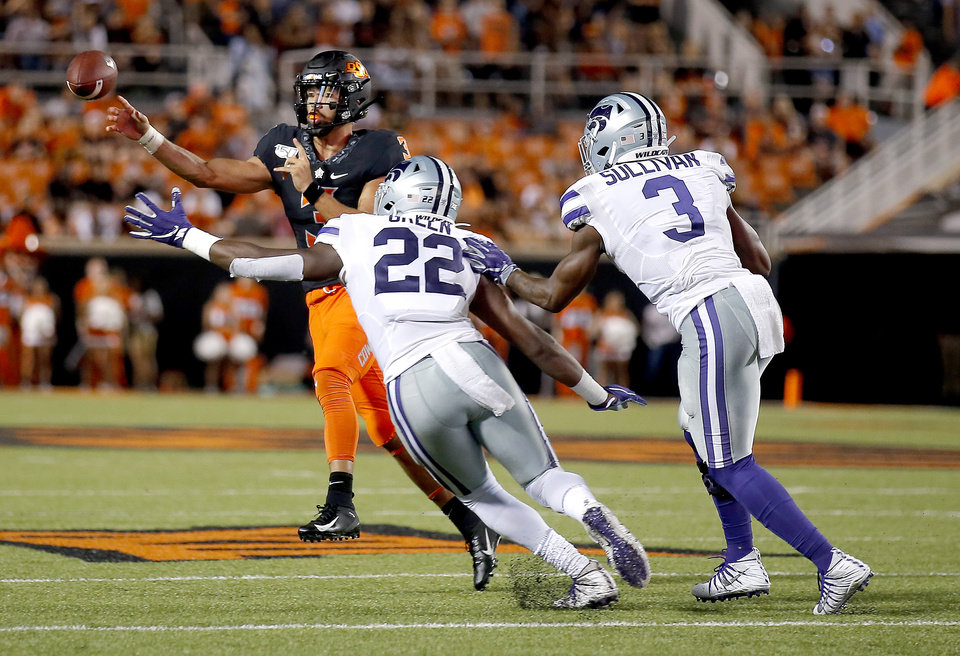 Photo - Oklahoma State's Spencer Sanders (3) throws as he is pressured by Kansas State's Daniel Green (22) an dElijah Sullivan (3) during the college football game between the Oklahoma State Cowboys and the Kansas State Wildcats at Boone Pickens Stadium in Stillwater, Okla., Saturday, Sept. 28, 2019. [Sarah Phipps/The Oklahoman]