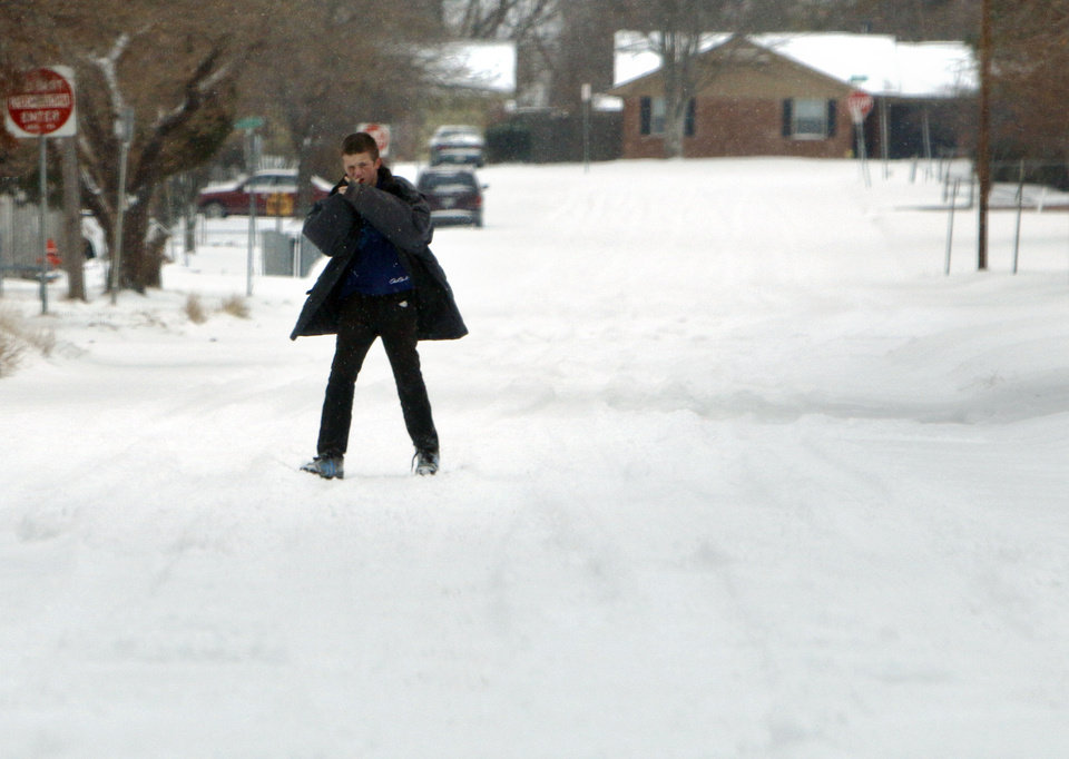 A pedestrian walks a snow-packed street in north Oklahoma City, OK, Friday, December 6, 2013,  Photo by Paul Hellstern, The Oklahoman