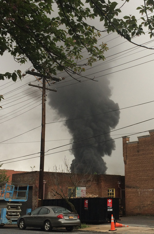Photo - In this mobile phone photo provided Charles Peters, smoke rises after several CSX tanker cars carrying crude oil derailed on Wednesday, April 30, 2014, in Lynchburg, Va. Authorities evacuated numerous buildings Wednesday after the derailment. (AP Photo/Charles Peters) MANDATORY CREDIT