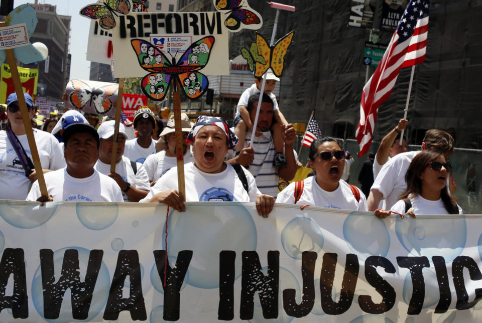 Photo - Car wash workers with the Community Labor Environmental Action Network (CLEAN) Carwash Campaign march during a May Day rally in downtown Los Angeles on Wednesday, May 1, 2013. In celebration of May Day, people have gathered across the country to rally for various topics including immigration reform. (AP Photo/Damian Dovarganes)