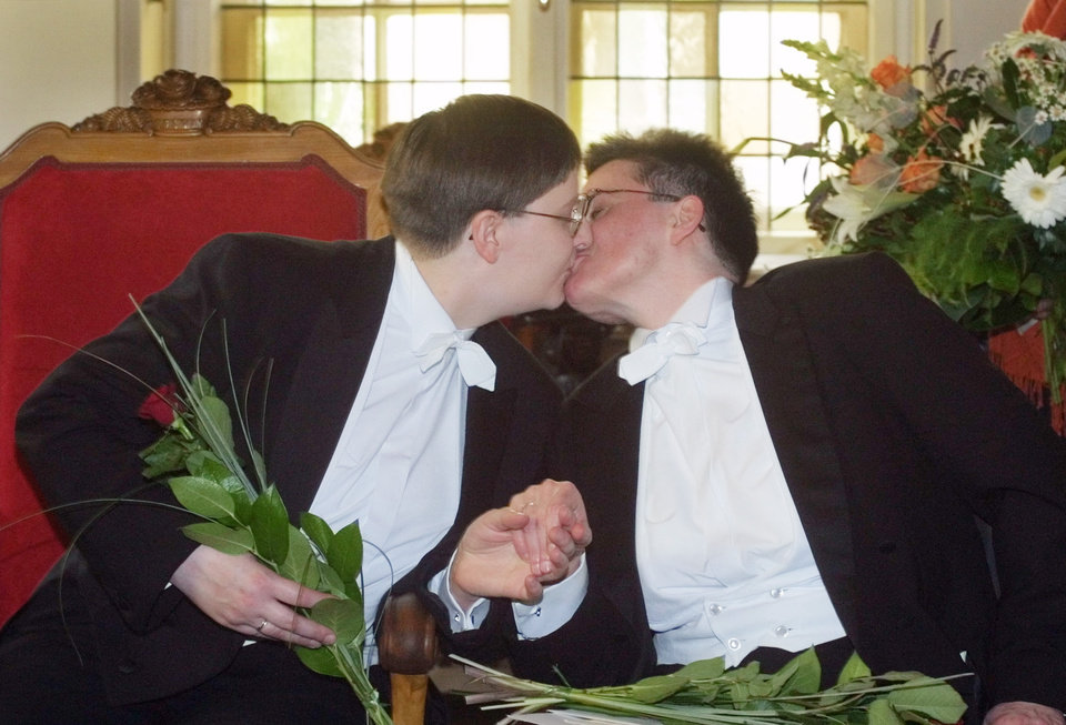 FILE - In this Aug. 1, 2001 file picture German lesbian couple Gudrun Pannier, left, and Angelika Baldow, right, kiss each other in the Rathaus Schoeneberg, city hall, in Berlin . Pannier and Baldow were the first gay couple in Berlin who exchanged vows at a partnership ceremony to receive some of the same rights as heterosexual marriages under a new law that went into effect on Aug. 1, 2001.  Gay rights campaigners won a victory in Germany on Thursday June 6, 2013 when the country's top court ordered the government to grant homosexual civil unions the same tax benefits as heterosexual married couples. The Federal Constitutional Court in Karlsruhe ruled that treating the two forms of partnership differently for tax purposes violates the country's guarantee of equal rights. (AP Photo/Markus Schreiber, File )