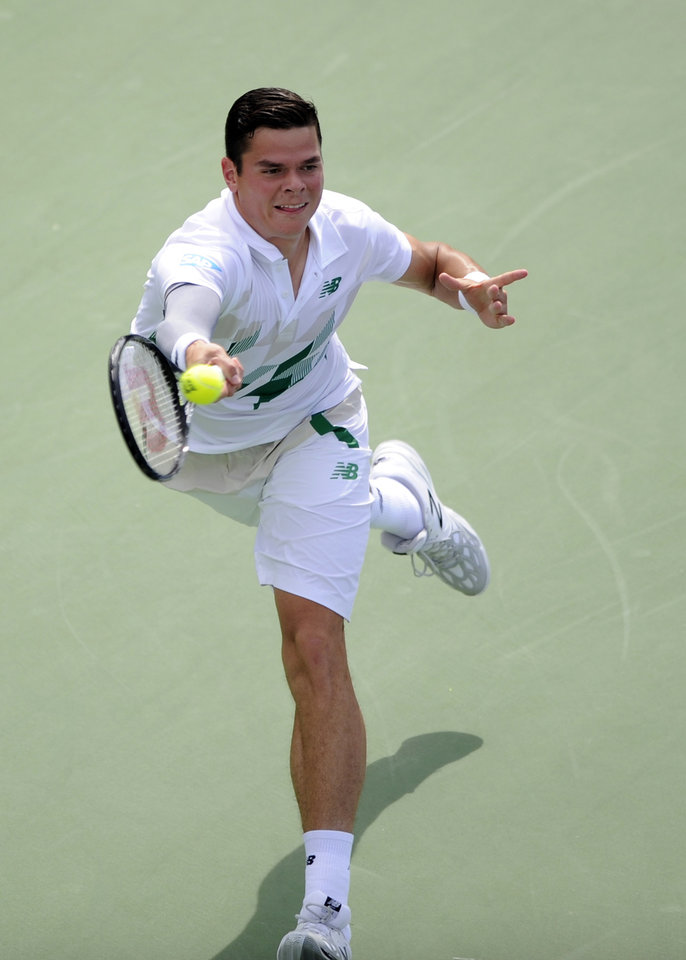 Photo - Milos Raonic, of Canada, returns a shot against Donald Young during a match at the Citi Open tennis tournament, Saturday, Aug. 2, 2014, in Washington. Raonic won 6-4, 7-5.  (AP Photo/Nick Wass)