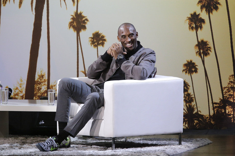 Photo - Los Angeles Lakers' Kobe Bryant laughs while talking to talk show host Jimmy Kimmel during a one-on-one conversation at Nokia Theatre on Thursday, Aug. 15, 2013, in Los Angeles. The event was held to raise money toward eliminating homelessness in the Los Angeles area. (AP Photo/Jae C. Hong)