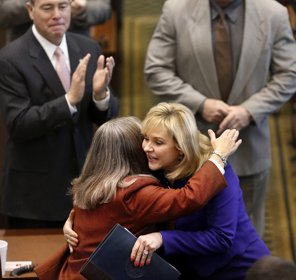 Photo - Gov. Mary Fallin is greeted by Rep. Sally Kern with a hug as the governor passes Kern's desk on her way to the podium.  Fallin outlined her goals for the upcoming legislative session during her state of the state speech to a joint session of the legislature in the House chamber at the state Capitol on Monday, Feb. 3, 2014.   Photo by Jim Beckel, The Oklahoman