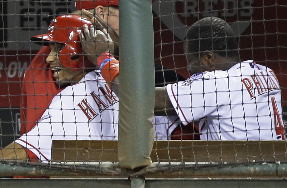 Cincinnati Reds' Billy Hamilton is congratulated by Brandon Phillips (4) in the dugout after Hamilton scored the only run of the baseball game, in the seventh inning against the St. Louis Cardinals, Tuesday, Sept. 3, 2013, in Cincinnati. Cincinnati won 1-0. (AP Photo/Al Behrman)