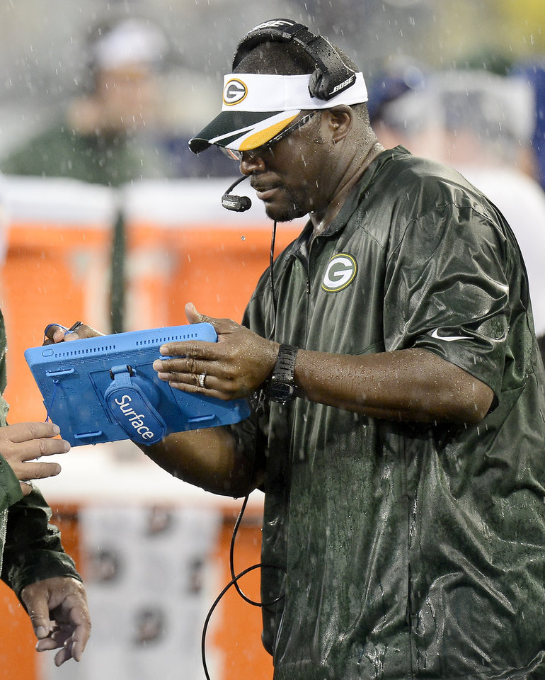 Photo - In this Aug. 9, 2014 photo, Green Bay Packers wide receivers coach Edgar Bennett uses a computer pad in a rainstorm during a preseason NFL football game against the Tennessee Titans in Nashville, Tenn. The tablets, designed to survive all sorts of weather, are equipped to look at still photos of game action. (AP Photo/Mark Zaleski)