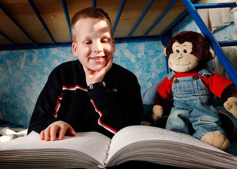 Photo - BLIND / BLINDNESS: Daniel Brookshire, a Tulsa eighth-grader, sits on his bed with one of the Braille volumes of the Bible in his family's home  on Thursday, Jan. 7, 2010. Photo by Jim Beckel, The Oklahoman ORG XMIT: KOD