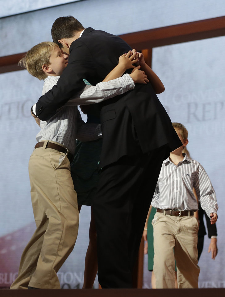 Photo -   Republican vice presidential nominee, Rep. Paul Ryan hugs his children, from left, Sam and Liza, as Charlie, right, and wife Janna walk up to him after his acceptance speech during the Republican National Convention in Tampa, Fla., on Wednesday, Aug. 29, 2012. (AP Photo/Charles Dharapak)