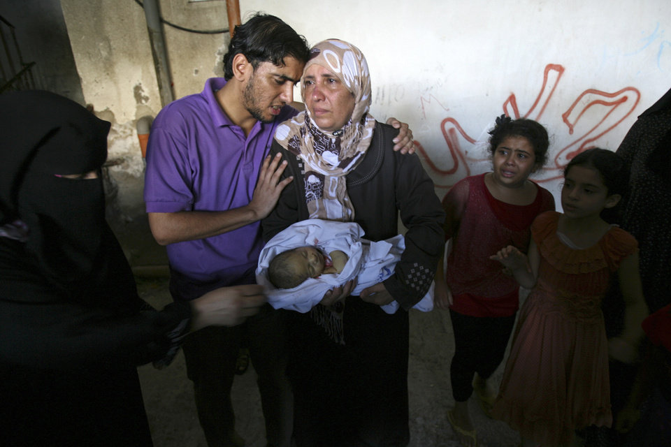 Photo - A relative carries a dead baby during the funeral of members of Al Ghoul family in the Rafah refugee camp, in the southern Gaza Strip, Sunday, Aug. 3, 2014. At least 40 people were inside the Al Ghoul family building in Rafah when it was targeted by Israeli jet fighters, according to the Red Crescent and Gaza health official Ashraf al-Kidra. Many have been confirmed dead and over two dozen have been wounded. (AP Photo/Hatem Ali)