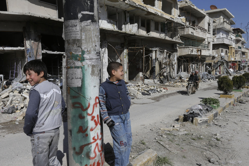 Photo - Syrian boys, stand in  a destroyed street which was damaged by the shelling of the Syrian forces, at Maarat al-Nuaman town, in Idlib province, Syria, Tuesday Feb. 26, 2013. Syrian rebels battled government troops near a landmark 12th century mosque in the northern city of Aleppo on Tuesday, while fierce clashes raged around a police academy west of the city, activists said. the Arabic words read: