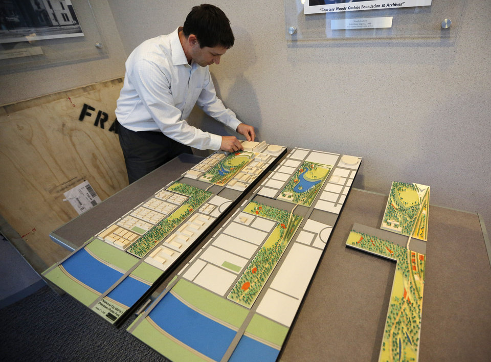 Photo - Ben Kuchinsky, a consultant with Hargreaves Associates, prepares models Thursday of the three design ideas for the MAPS 3 urban park before a public meeting in Oklahoma City. One idea, left, concentrates programmed parts of the park in the north and more landscaping in the south. A second, center, spreads nodes of programming throughout the park. The third, right, keeps programmed parts on the eastern edge and natural parts on the western edge.  GARETT FISBECK - The Oklahoman