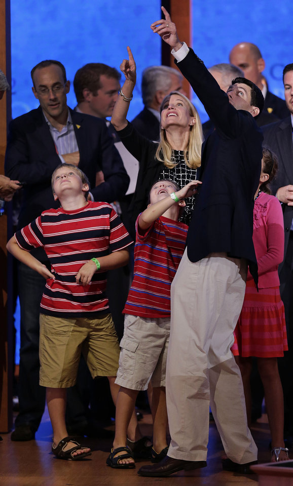 Photo -   Republican vice presidential nominee, Rep. Paul Ryan of Wisconsin points out the balloons with his wife Janna to their children, (L-R), Charlie, Sam and Liza during a podium sound check at the Republican National Convention in Tampa, Fla., on Wednesday, Aug. 29, 2012. (AP Photo/J. Scott Applewhite)