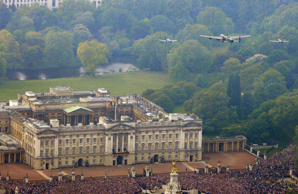 Photo - In this im,age made available by the Ministry of Defence, the Battle of Britaion memorial Flight, comprising of a Spitfire, left, Hurricane, right,  and Lancaster bomber, flies over Buckingham Palace as Britain's Prince William and his wife, Kate, Duchess of Cambridge appear on the balcony, following  their wedding at London's Westminster Abbey, Friday April 29, 2011.(AP Photo/Neil Chapman, Ministry of Defence, ho)  EDITORIAL USE ONLY: ORG XMIT: RWAT124