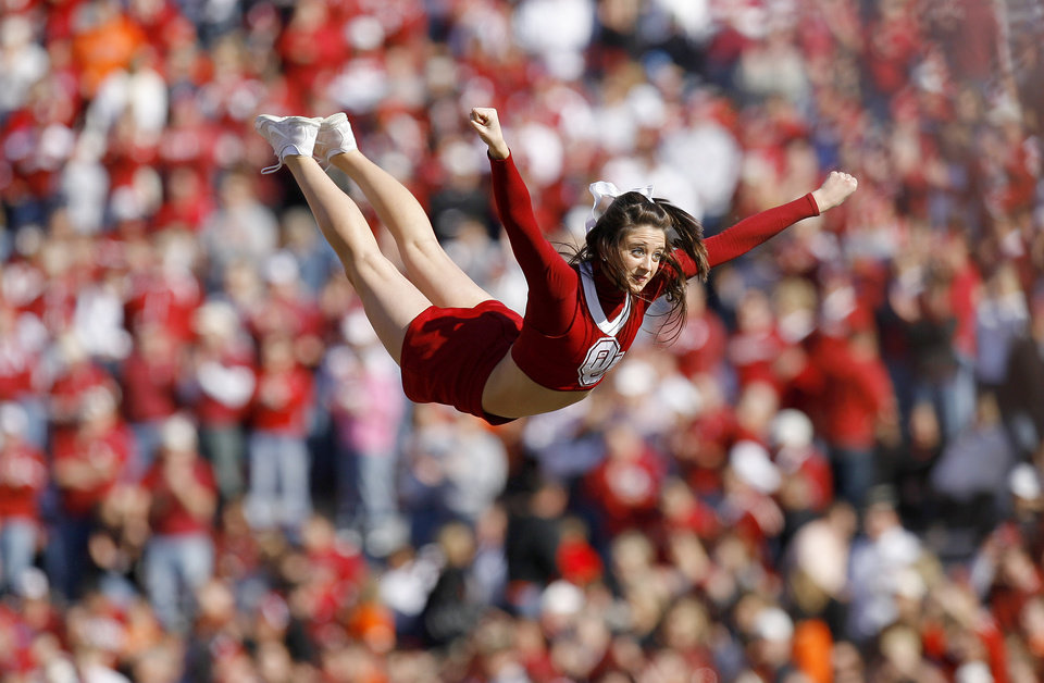 Photo - An OU cheerleader flies through the air during the first half of the Bedlam college football game between the University of Oklahoma Sooners (OU) and the Oklahoma State University Cowboys (OSU) at the Gaylord Family-Oklahoma Memorial Stadium on Saturday, Nov. 28, 2009, in Norman, Okla.Photo by Bryan Terry, The Oklahoman